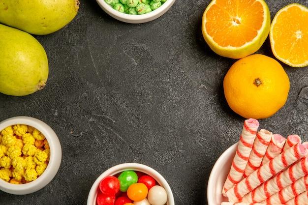 Vista dall'alto di frutta fresca con caramelle su grigio scuro