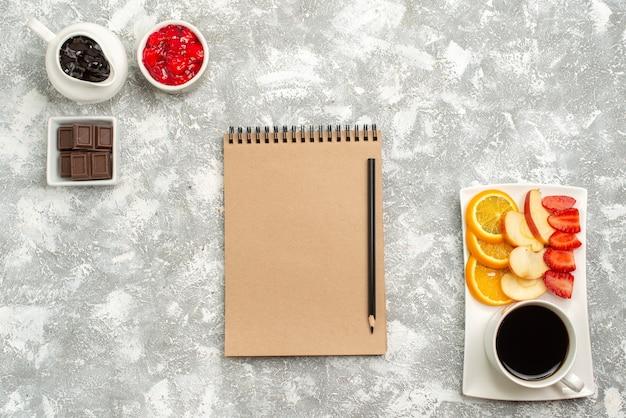 Вид сверху свежие фрукты с чашкой кофе и джемом на белом фоне фруктовые закуски, варенье, кофе