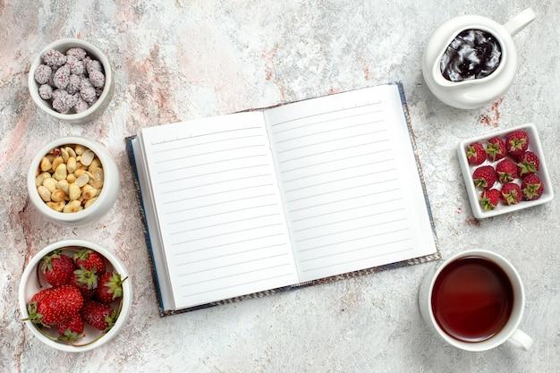 Вид сверху свежие фрукты с орехами и чашкой чая на белом фоне ореховые фрукты ягоды чайные конфеты