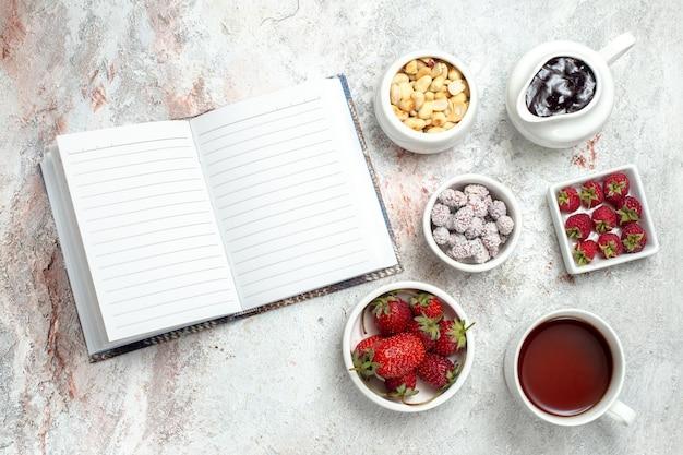 Vista dall'alto frutta fresca con noci e tazza di tè su sfondo bianco caramelle al tè con bacche di frutta a guscio