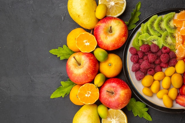 Top view fresh fruits with sliced fruits inside plate on a dark background