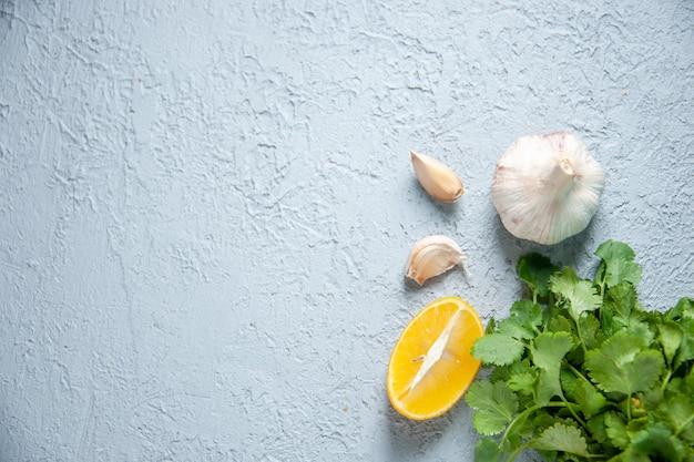 Вид сверху свежий чеснок с зеленью и лимоном на светлом фоне пищевое растение перец кислая приправа овощ