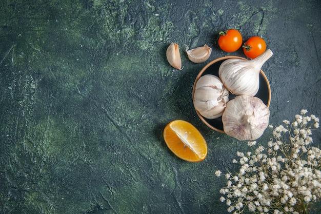 Vista dall'alto aglio fresco con pomodori su sfondo grigio pianta vegetale condimento acido verdi cibo pepe