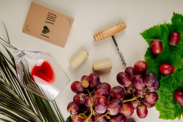 Top view of fresh grape , small postcard, bottle screw with wine corks and a wine glass lying on white table