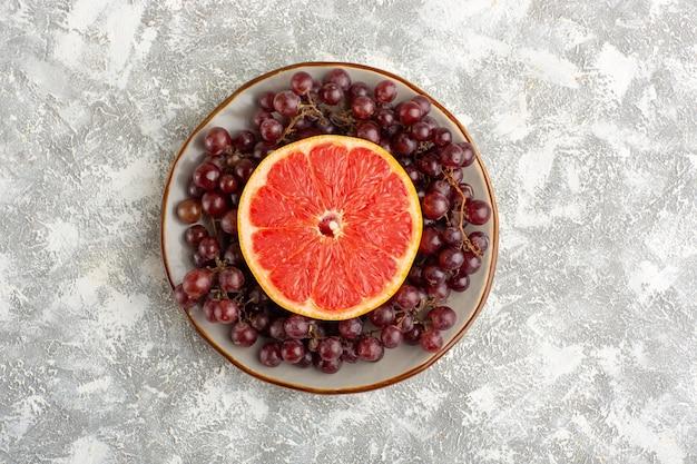白い机の上に赤いブドウとトップビューの新鮮なグレープフルーツリング
