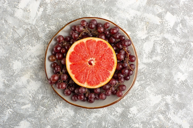 Top view fresh grapefruit ring with red grapes on the white desk
