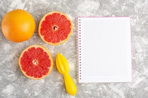 Вид сверху кольца свежего грейпфрута с блокнотом на светлой белой поверхности