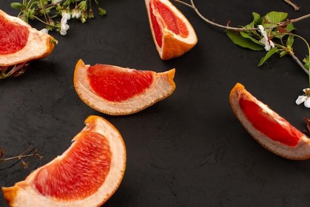 トップビューフレッシュなグレープフルーツのスライスは、暗い床に分離されたまろやかな熟したジューシーです