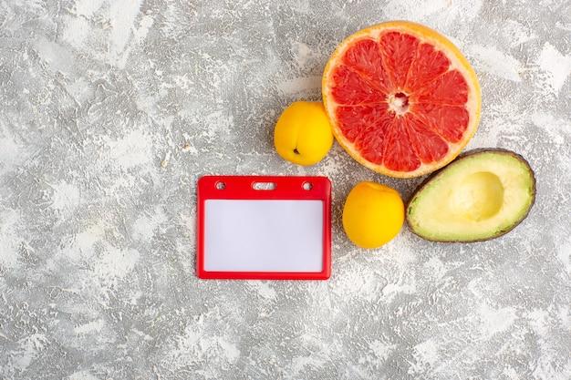 Вид сверху свежие грейпфруты, спелые и сочные цитрусы с авокадо на белой поверхности
