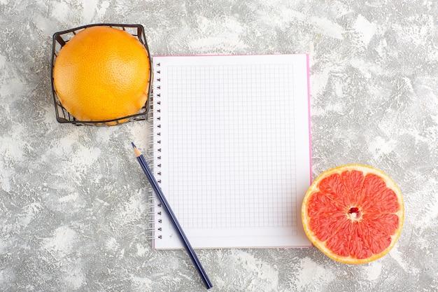 Вид сверху свежие грейпфруты с блокнотом на белой поверхности