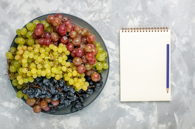上面図新鮮なブドウジューシーでまろやかなフルーツ、明るい白の背景のプレート内フルーツまろやかなジュースワイン新鮮
