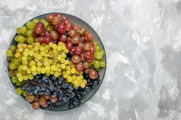 Vista superiore dell'uva fresca frutta succosa e pastosa all'interno della piastra sullo sfondo bianco frutta mellow succo di vino fresco