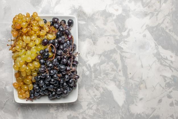상위 뷰 신선한 포도 흰색 배경에 접시 안에 부드럽고 달콤한 과일 과일 신선한 와인 포도 주스 나무
