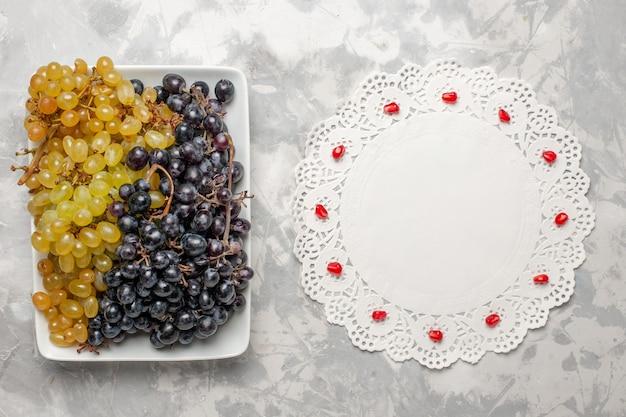 상위 뷰 신선한 포도 흰색 표면에 접시 안에 부드럽고 달콤한 과일 신선한 와인 포도 주스 나무