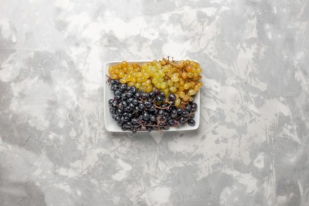 Vista superiore dell'uva fresca frutta pastosa e succosa all'interno del piatto sulla superficie bianca frutta fresca vino succo d'uva albero