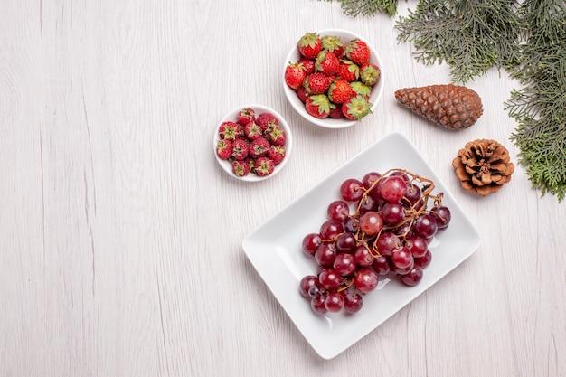 Vista dall'alto di uva fresca con frutti di bosco su tavola di legno