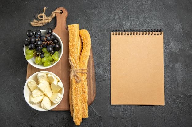 上面図新鮮なブドウとチーズとパン、暗い表面の果物まろやかな熟した木のビタミン食品ミルク