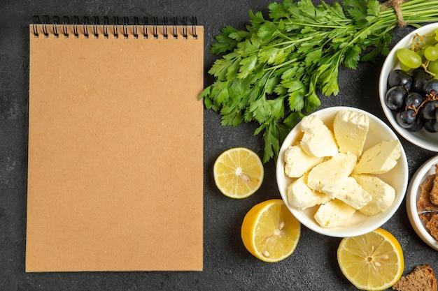 暗い表面の食事の朝食の皿のミルクフルーツのチーズグリーンおよびレモンスライスが付いている上面図の新鮮なブドウ
