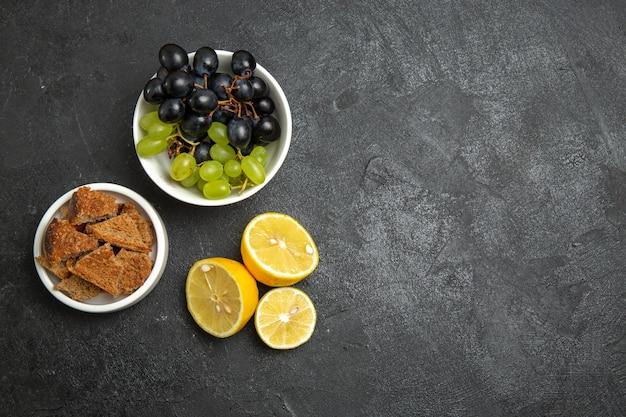 어두운 표면 과일 부드러운 익은 나무 비타민에 레몬 조각과 상위 뷰 신선한 포도