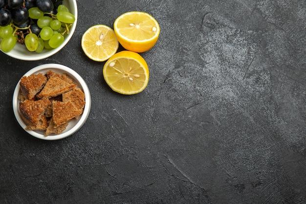 어두운 표면 과일에 레몬 조각을 넣은 상위 뷰 신선한 포도는 잘 익은 나무 비타민을 부드럽게 합니다.
