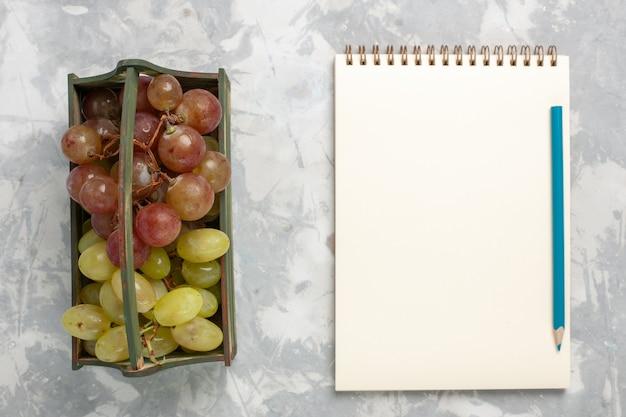 Uva fresca vista dall'alto con il blocco note su sfondo bianco frutta fresca succosa dolce