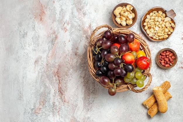 Vista dall'alto di uve fresche con noci sulla superficie bianca