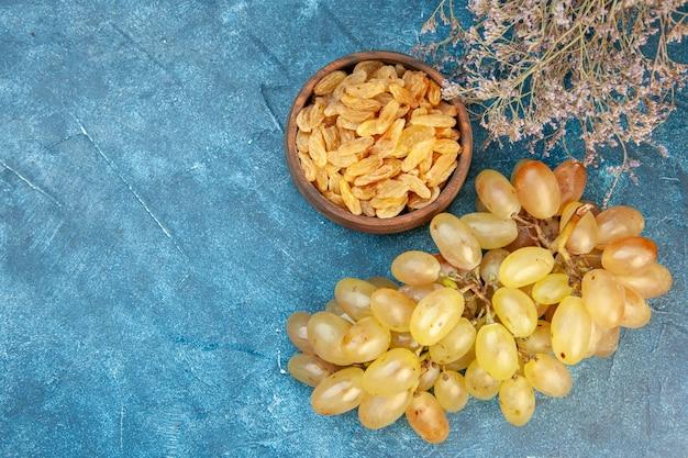 Vista dall'alto uva fresca con uvetta sul tavolo blu