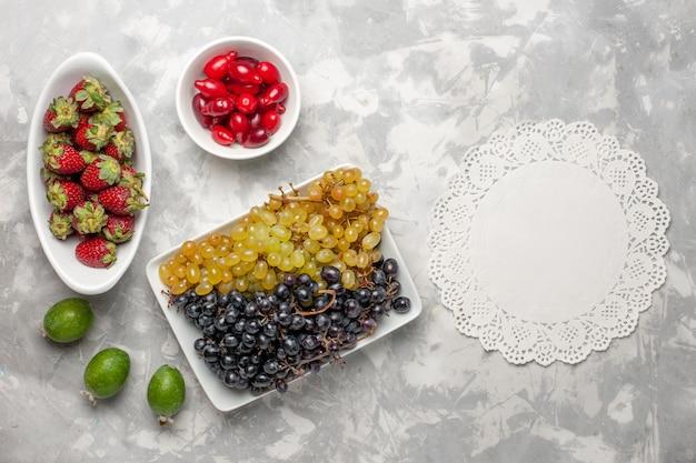 上面図白い表面の果物のまろやかなビタミンジュースにイチゴとハナミズキと新鮮なブドウ