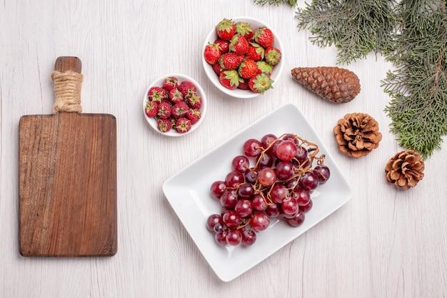 Vista dall'alto di uva fresca con fragole e lamponi sul tavolo bianco