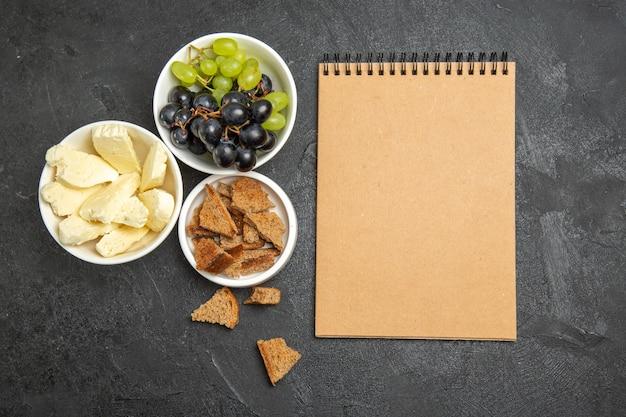 上面図新鮮なブドウと白いチーズ、暗い表面の食事朝食皿ミルクフルーツにスライスした暗いパン