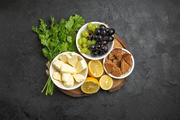暗い表面に白いチーズグリーンとレモンスライスを添えた新鮮なブドウの上面図食事フルーツミルク食品