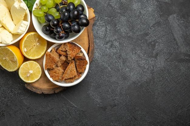 ダークグレーの表面の食事フルーツミルク食品に白いチーズグリーンとレモンスライスを添えた新鮮なブドウの上面図