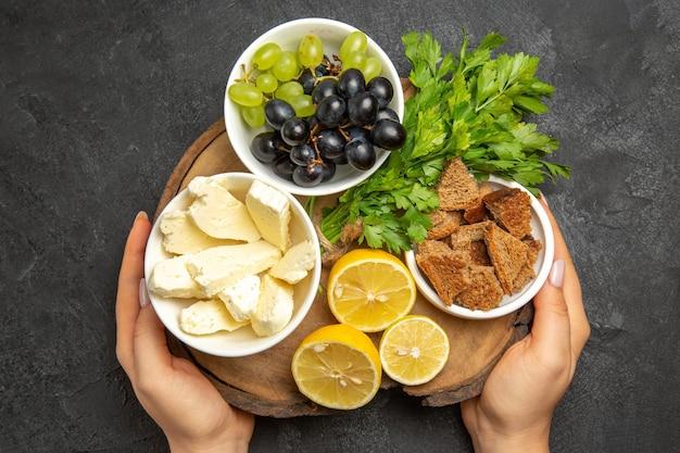 어두운 표면 음식 우유 과일에 흰색 치즈 레몬 조각과 녹색을 곁들인 신선한 포도