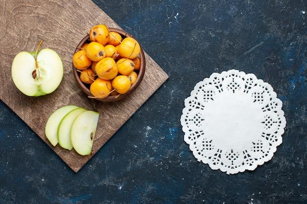 Vista dall'alto della mela verde fresca tagliata a metà affettata con ciliegie dolci sulla scrivania scura, frutta fresca e matura