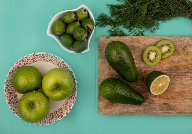 Vista dall'alto di mele verdi fresche su una ciotola con feijoas su una ciotola con avocado limette e kiwi su una tavola da cucina in legno su una parete blu