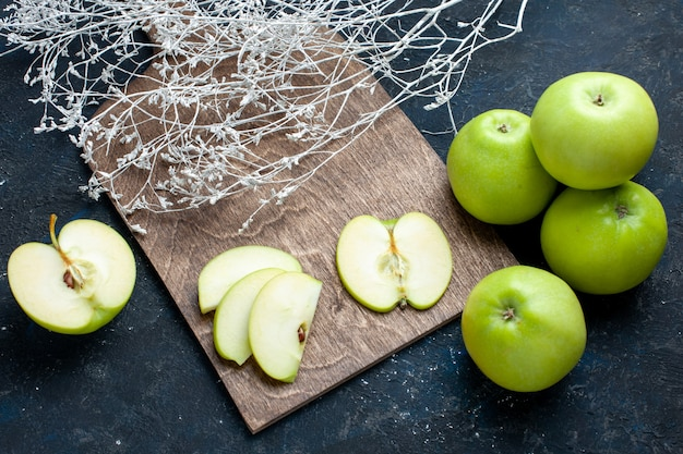 Top view of fresh green apples composition with half-cut sliced one lined on dark, fruit fresh mellow