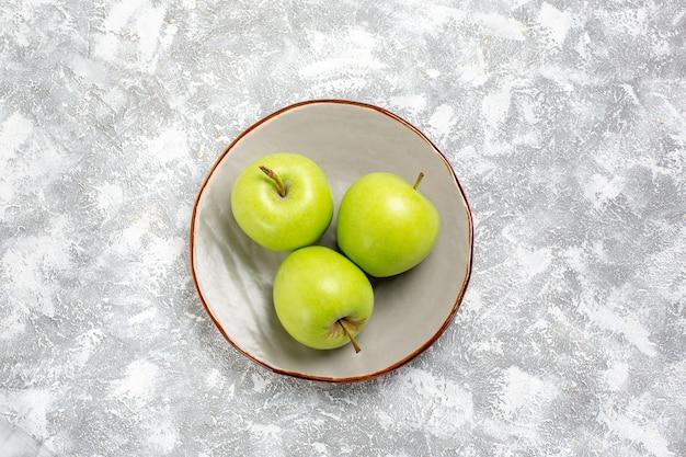 明るい白い表面のプレート内の上面図新鮮な青リンゴ