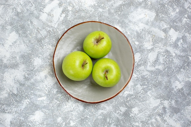 Top view fresh green apples inside plate on white surface