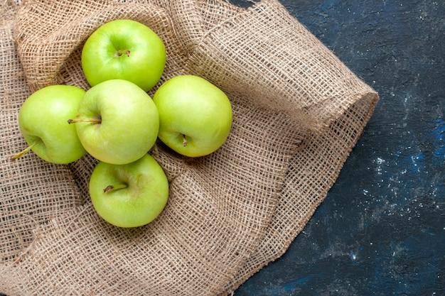 Vista dall'alto di mele verdi fresche pastose e succose acide sulla scrivania blu scuro, spuntino alimentare con vitamine per la salute della frutta