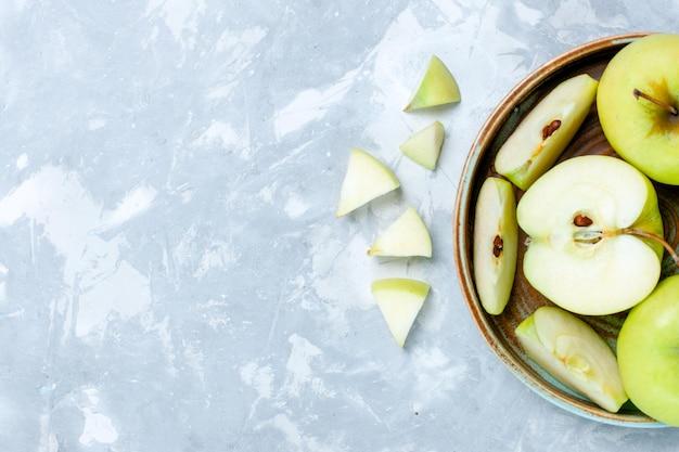 밝은 흰색 책상에 얇게 썬 신선한 녹색 사과와 전체 과일