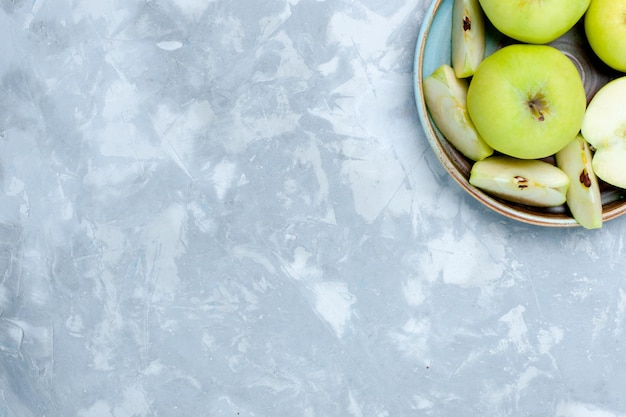 Top view fresh green apples sliced and whole fruits on light desk