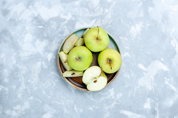 Top view fresh green apples sliced and whole fruits on light surface