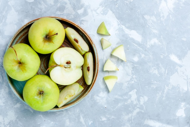 Top view fresh green apples sliced and whole fruits on light-white surface