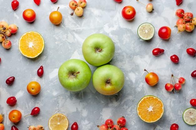Вид сверху свежие зеленые яблоки с лимоном и вишней на белом столе фруктовые ягоды витамин летний сочный