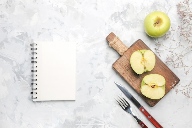 Top view fresh green apples with notepad on white background