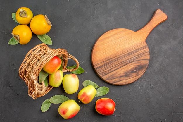 暗いテーブルの木に柿と新鮮な青リンゴの上面図まろやかな熟した新鮮な
