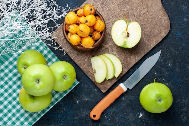 Vista dall'alto di mele verdi fresche con ciliegie dolci e pastose sulla scrivania scura, frutta fresca e pastosa