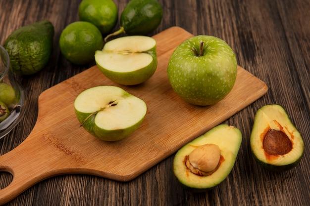Vista dall'alto di mele verdi fresche su una tavola di cucina in legno con avocado e limette isolato su una parete in legno