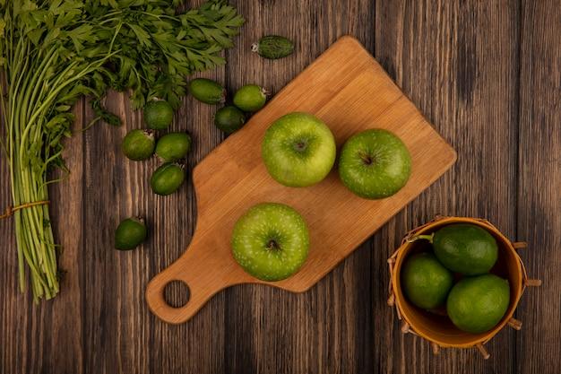 Vista dall'alto di mele verdi fresche su una tavola da cucina in legno con limette su un secchio con feijoas e prezzemolo isolato su una parete in legno