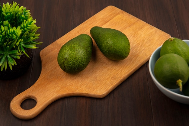 Top view of fresh green avocados on a wooden kitchen board with limes on a bowl on a wooden wall